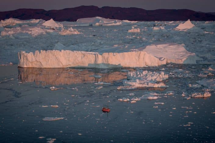 A passenger boat among the Ilulissat ice fjord icebergs in Greenland. By Mads Pihl