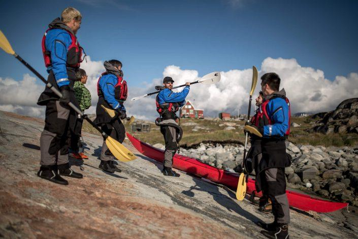 A PGI Greenland kayaking guide giving instructions to guests before going paddling in the Disko Bay. Photo by Mads Pihl
