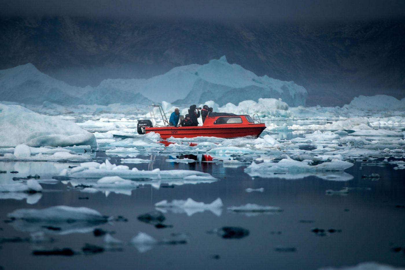 People on a boat taking photos of icebergs and mountains. Photo by Arctic Dream, Visit Greenland