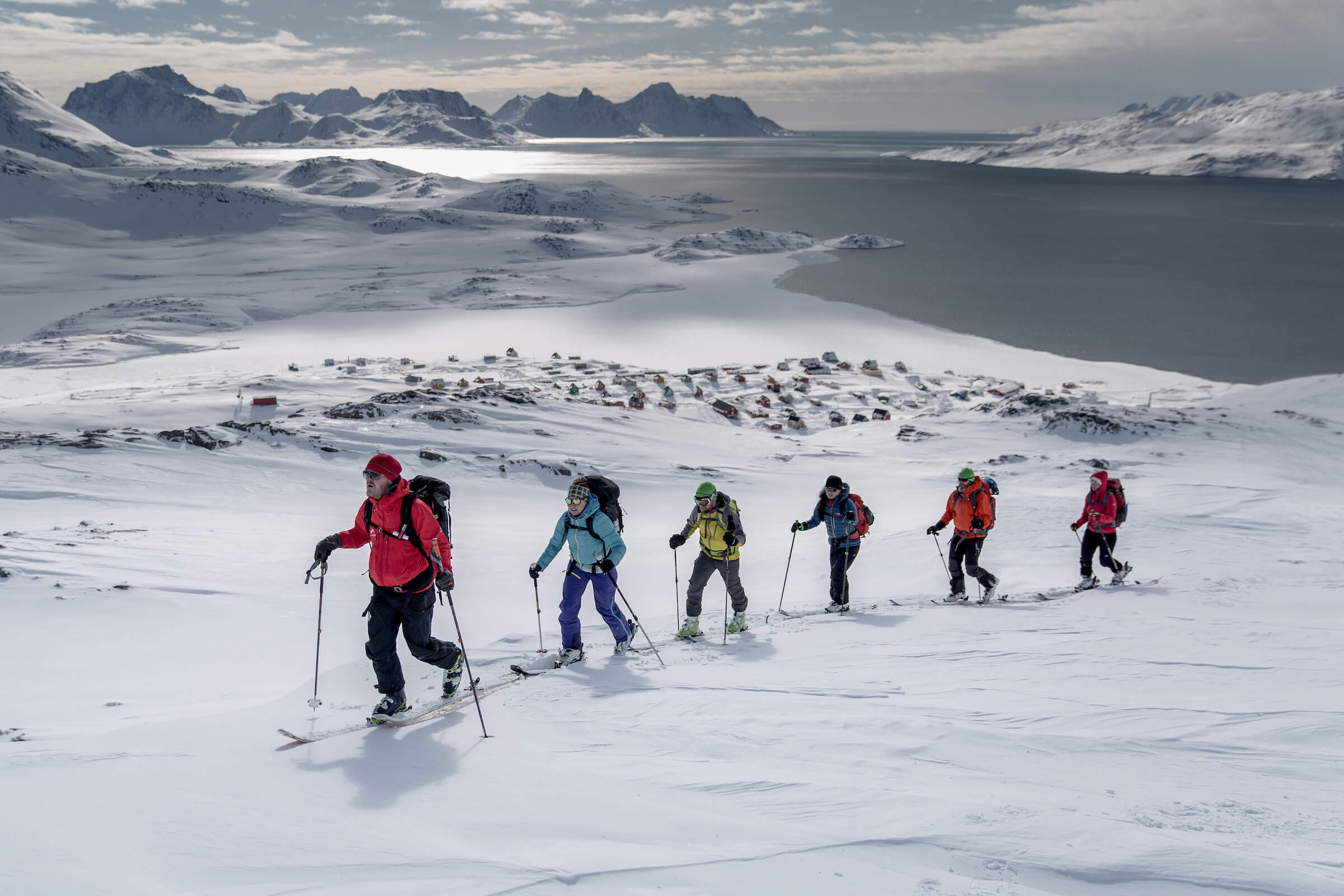 A group of skiers climbing a mountain near Kulusuk on a ski touring trip in East Greenland. Photo by Mads Pihl, Visit Greenland