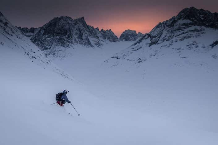 A skier descending from Tasiilaq Mountain Hut in the sunset in East Greenland. By Mads Pihl