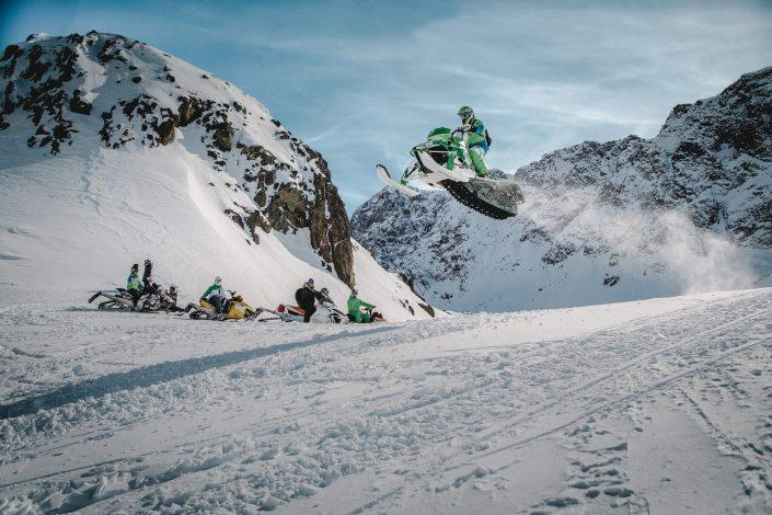 A snowmobiler flying high over a group of friends in the Sisimiut backckountry in Greenland. Photo by Mads Pihl.