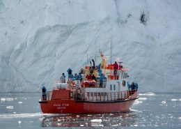 A tour boat in fron of an iceberg wall in the Ilulissat Icefjord in Greenland