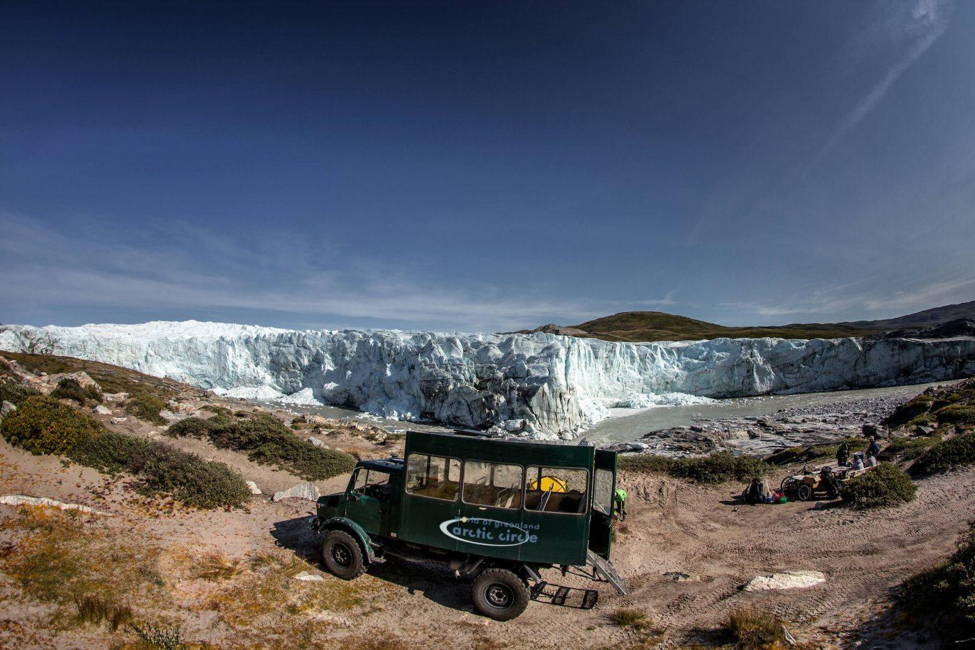 A tour bus from World of Greenland Arctic Circle parked by the Russell Glacier in Greenland. Photo by Mads Pihl