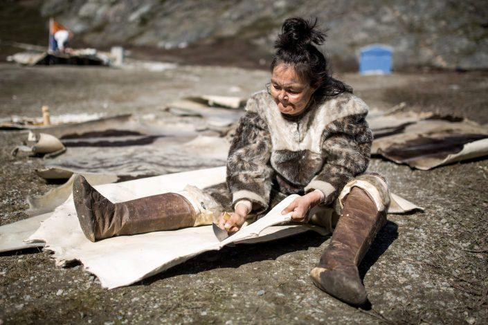 A woman carving seal skin for a tent at the living village museum in Qasigiannguit in Greenland. Photo by Mads Pihl