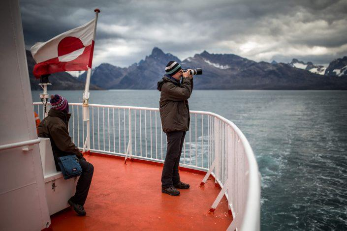 A photographer on the upper deck of Sarfaq Ittuk in Greenland