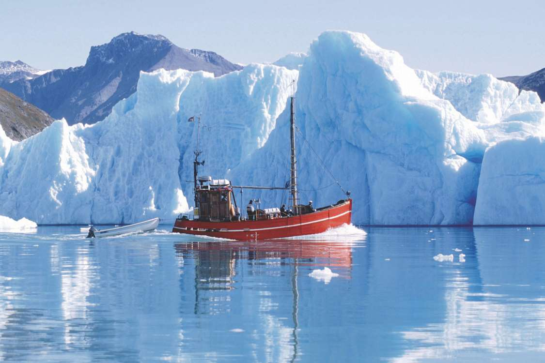 Saling vessel between icebergs in Greenland. Photo by Blue Ice Explorer