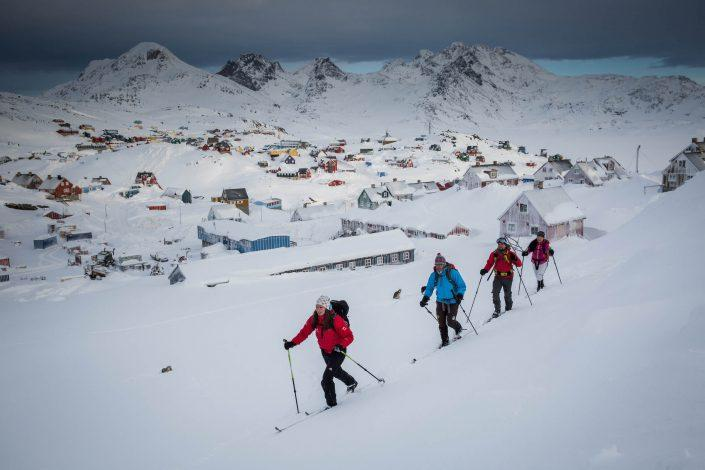 Cross country skiers on a hillside in Tasiilaq in East Greenland
