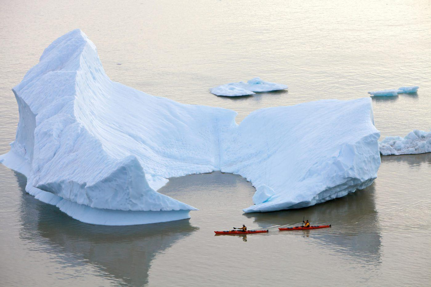 Kayakers rounding an iceberg in East Greenland. Photo by A Taste of Greenland