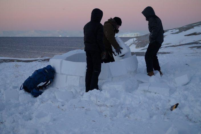 Guide and tourists building an iglo in North Greenland. Photo by Diskobay Adventures, Visit Greenland