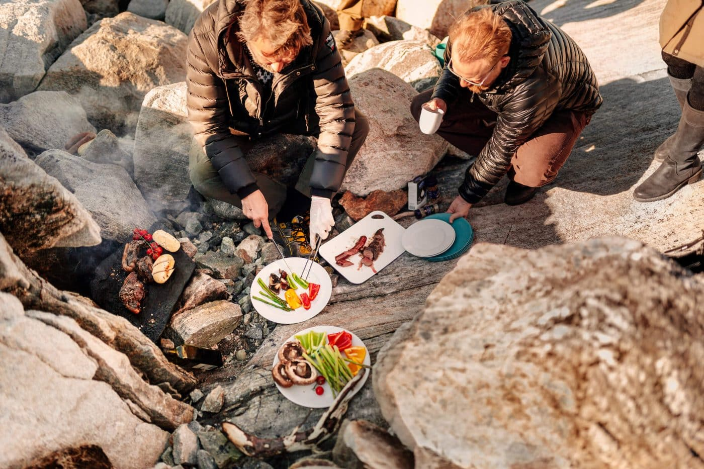 Friends preparing a meal on the rocks on the beach in Nuuk in Greenland. By Rebecca Gustafsson
