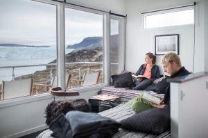 Guests enjoying a quiet moment in one of the Eqi Glacier Lodge comfort huts in Greenland