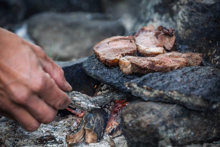 Greenland Outdoors guide cooks reindeer meat on the rocks in the Arctic Circle backcountry outside of Kangerlussuaq. By Raven Eye Photography