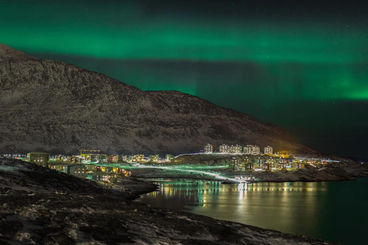 Northern Lights over the city lights of Qinngorput, Nuuk in Greenland. Photo by Rebecca Gustafsson