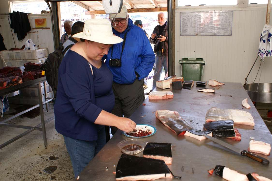 Tourists trying whale blubber and seal meat, local delicatessens, in Qaqortoq in South Greenland. Photo by Greenland Sagalands