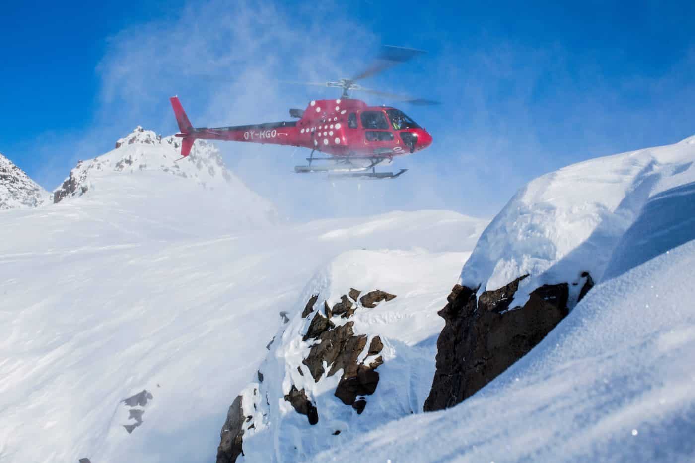 Air Greenland Helicopter hovering for skiers. By Jeremy Bernard