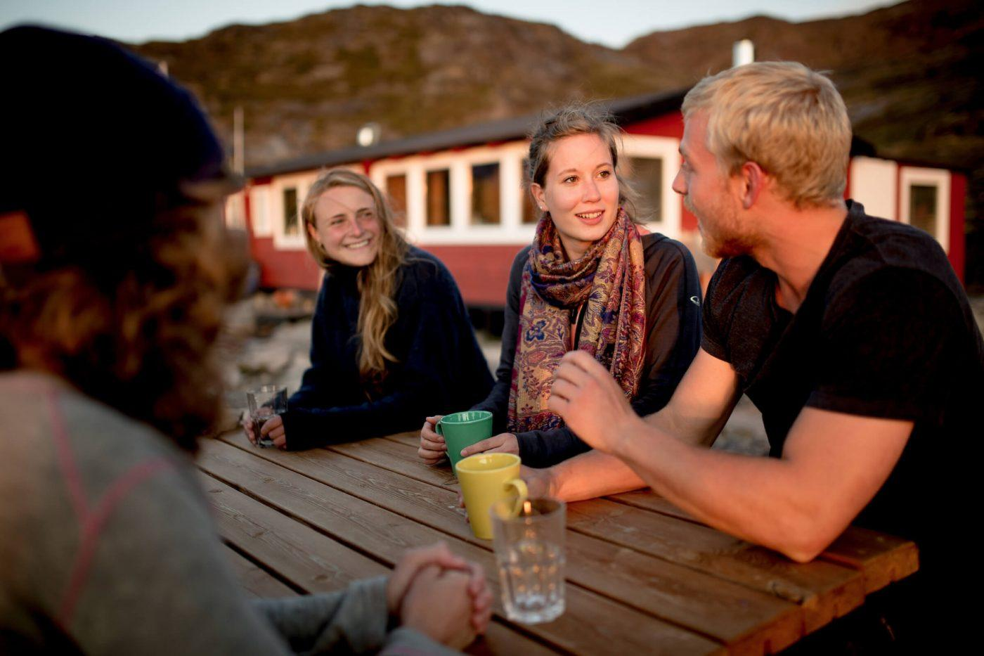 Guests in the sunset at Eqi Glacier Lodge in Greenland. Photo by Mads Pihl