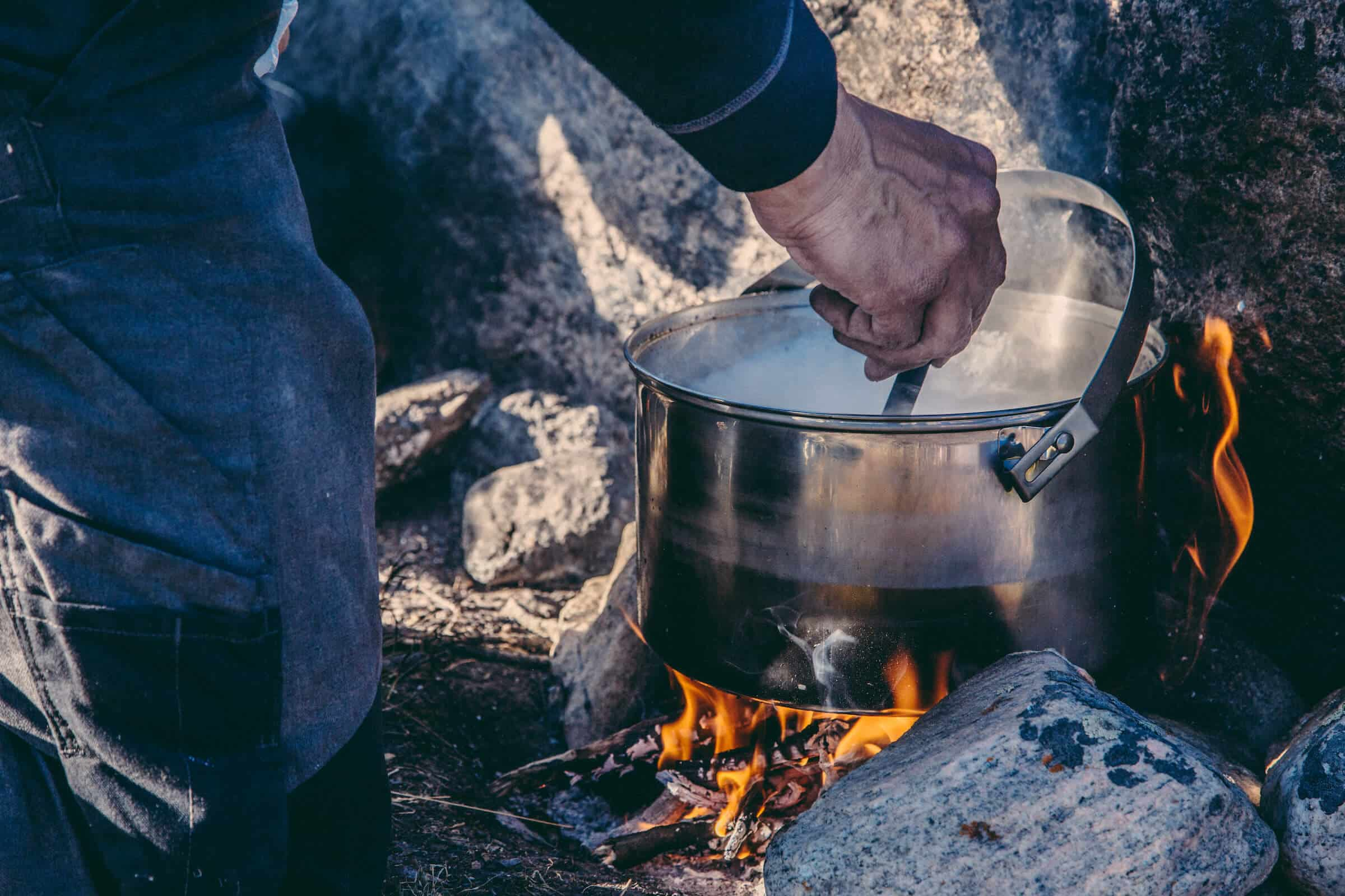 Guide cooking backcountry dinner over an open fire near the Arctic Circle. By Raven Eye Photography