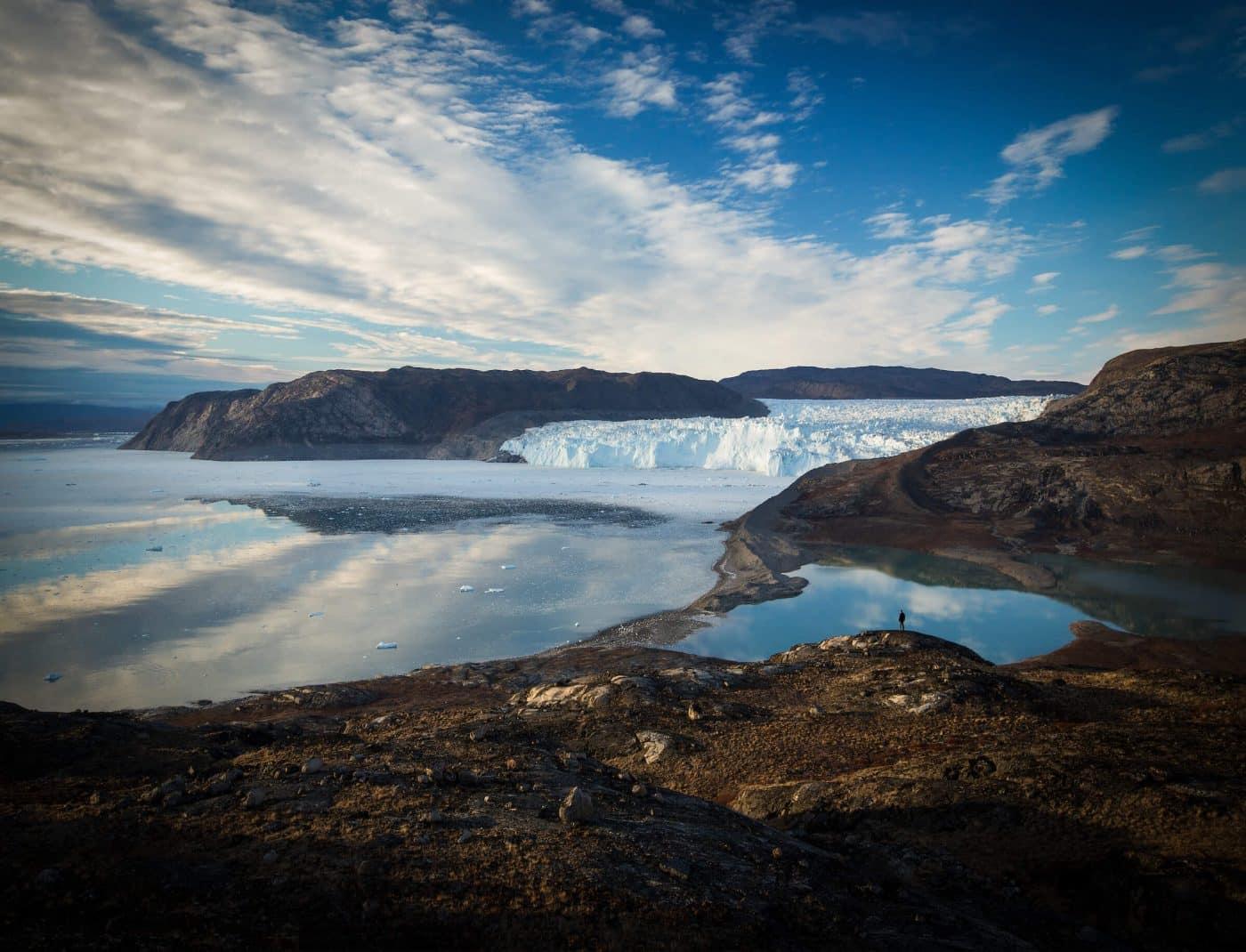 Hiker looks over Eqi Glacier near Ilulissat in North Greenland underneath the Midnight Sun. By Paul Zizka