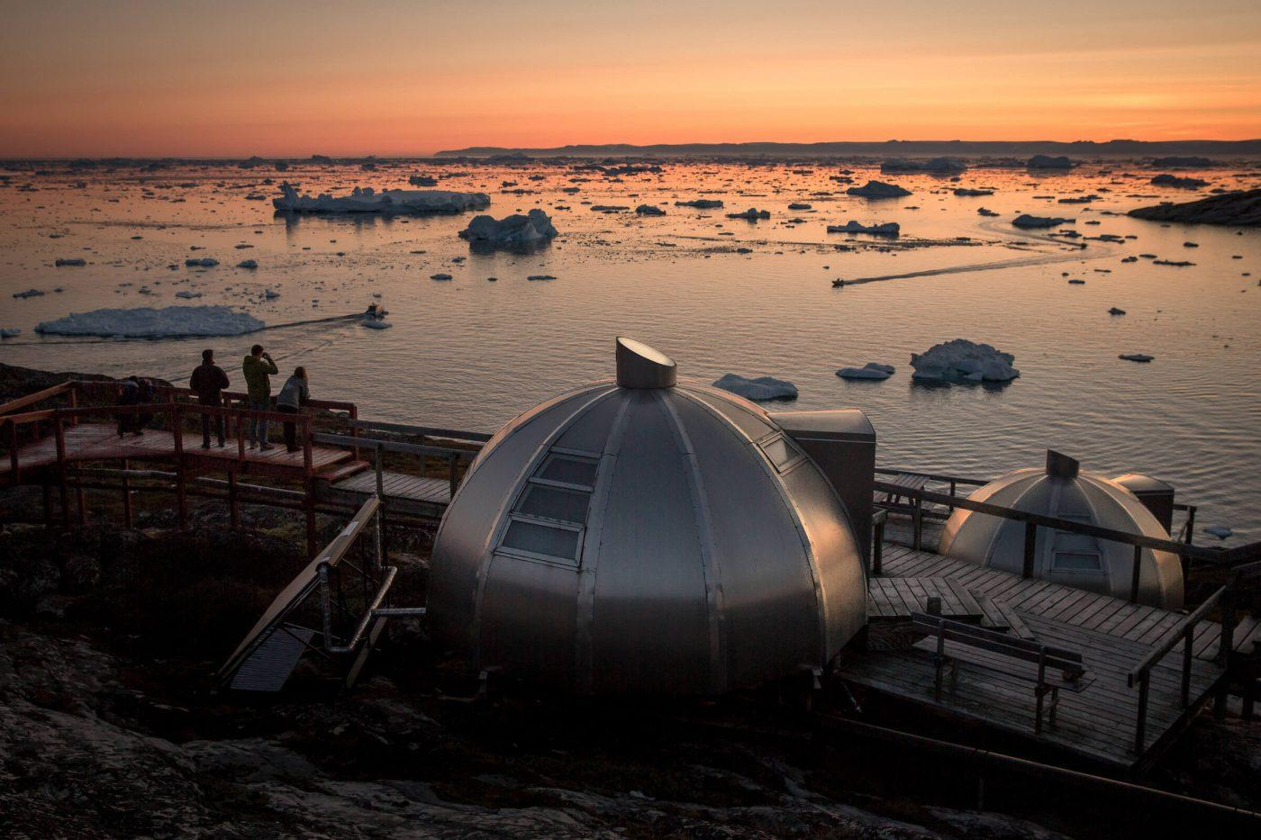 Photographers in the sunset near the Hotel Arctic igloos in Ilulissat in Greenland. Photo by Mads Pihl - Visit Greenland