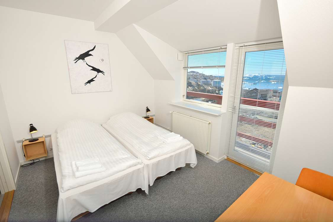 Room with double bed with a view of Ilulissat. Photo by Hotel Avannaa