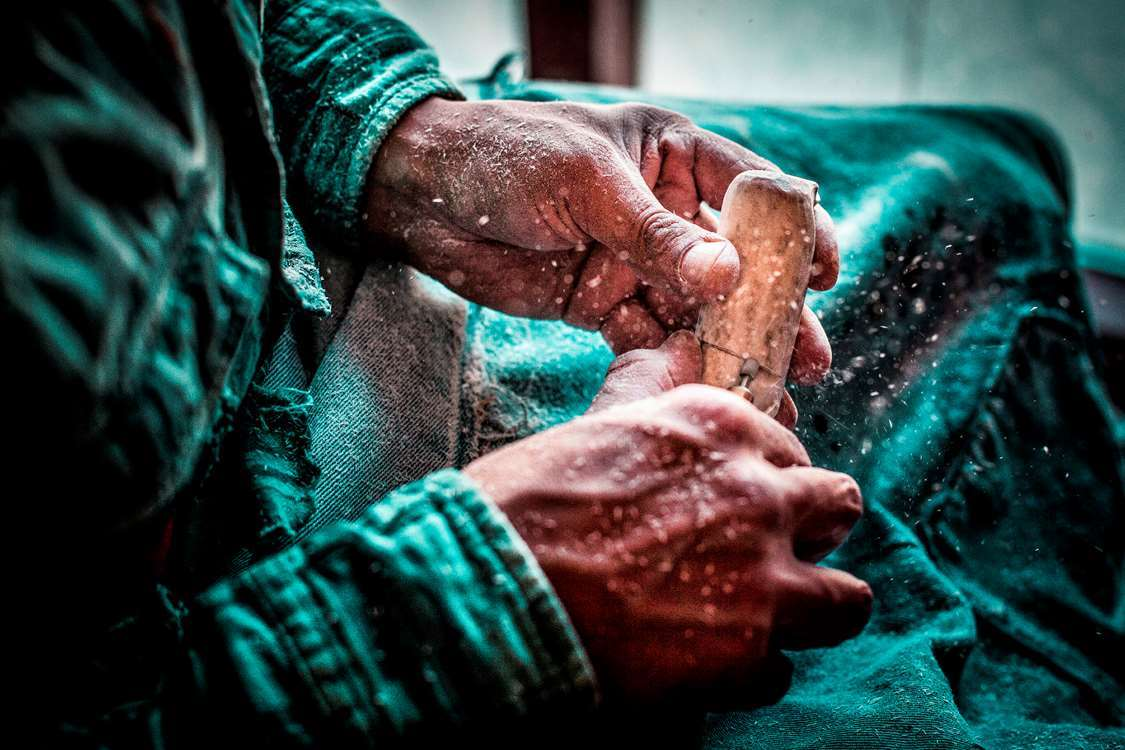 Enok Kilime carving reindeer bone in Sisimiut in Greenland. Photo by Mads Pihl, Visit Greenland