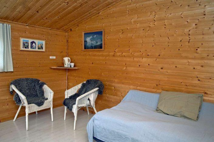 Room with double bed and lounge chairs. Photo by Igaliku Country Hotel - Visit Greenland