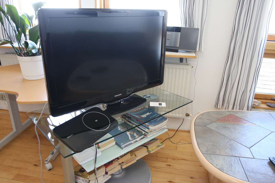 Large TV with books about Greenland and a couch table. Photo by Iherit Accommodation, Visit Greenland
