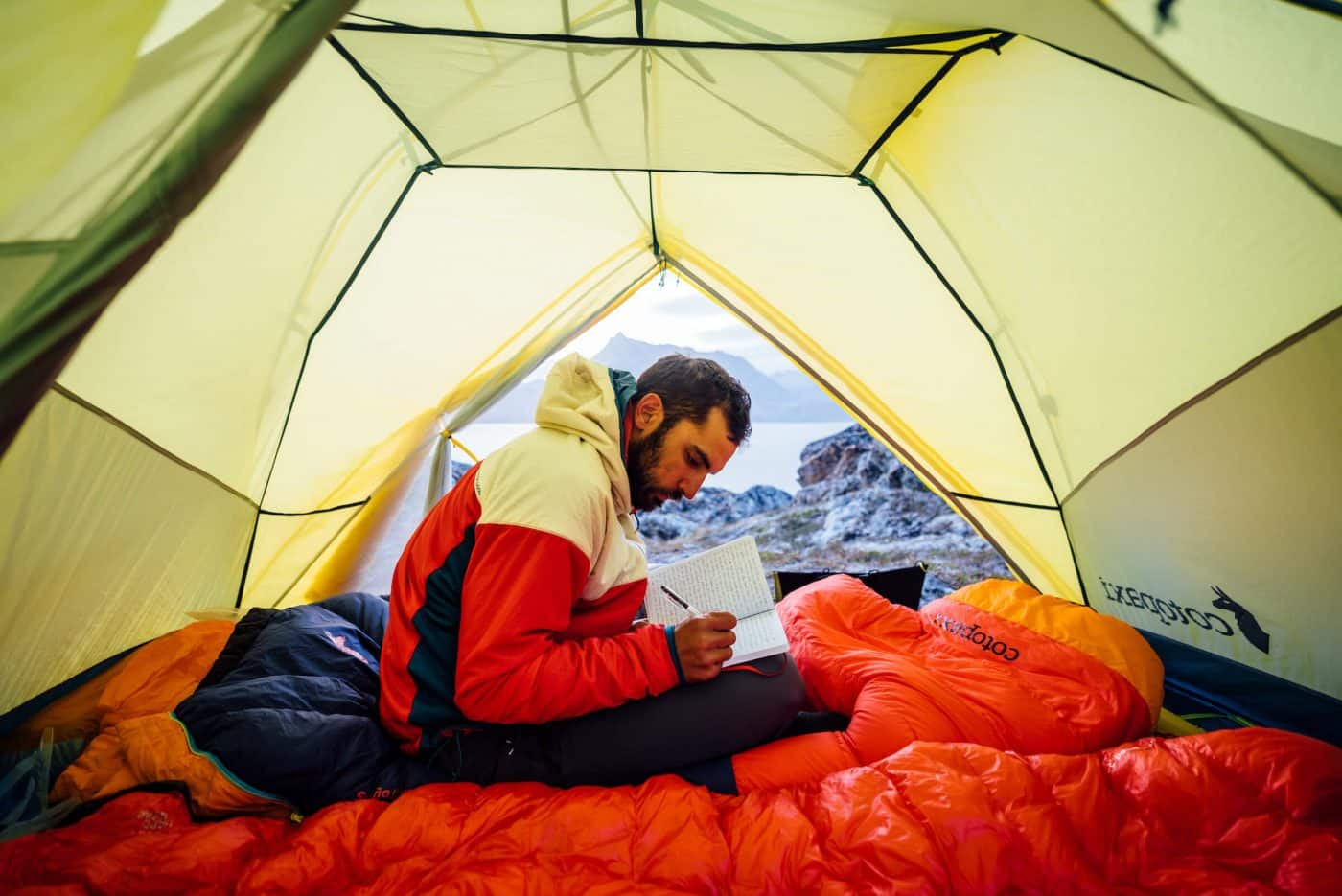 Inside a tent, a camper journals to his wife, water background, Between Kulusuk & Kuummiut. By Chris Brinlee Jr
