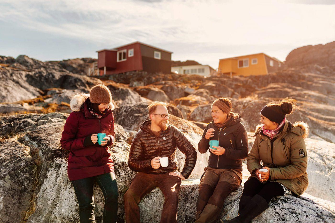 Group of friends drinking coffee on the beach by Inuk Hostels in Nuuk Greenland. Photo by Rebecca Gustafsson - Visit Greenland