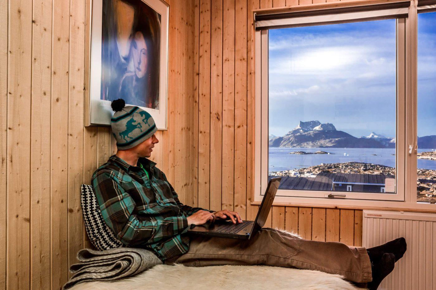 Traveler writes in his adventure log from the comfort of his bed at Inuk Hostels in Nuuk overlooking Nuuk Fjord and Sermitsiaq mountain. Photo by Raven Eye Photography - Visit Greenland