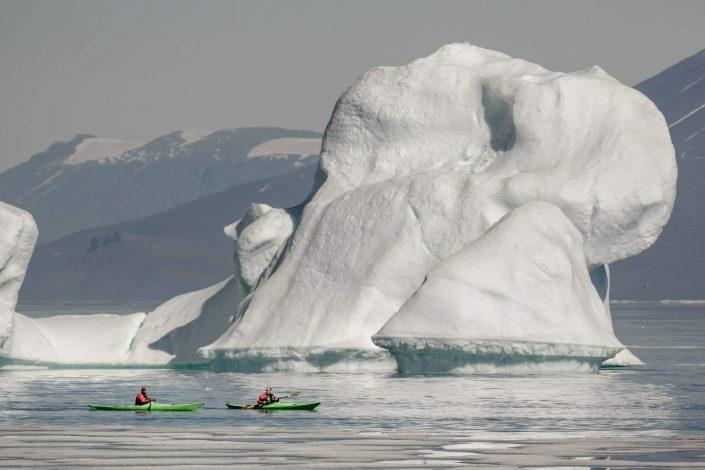 Kayakers near an iceberg in Illorsuit in North Greenland. By Mads Pihl