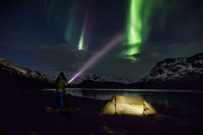 Man playing with norhern light and torch lamp, by Mads Pihl