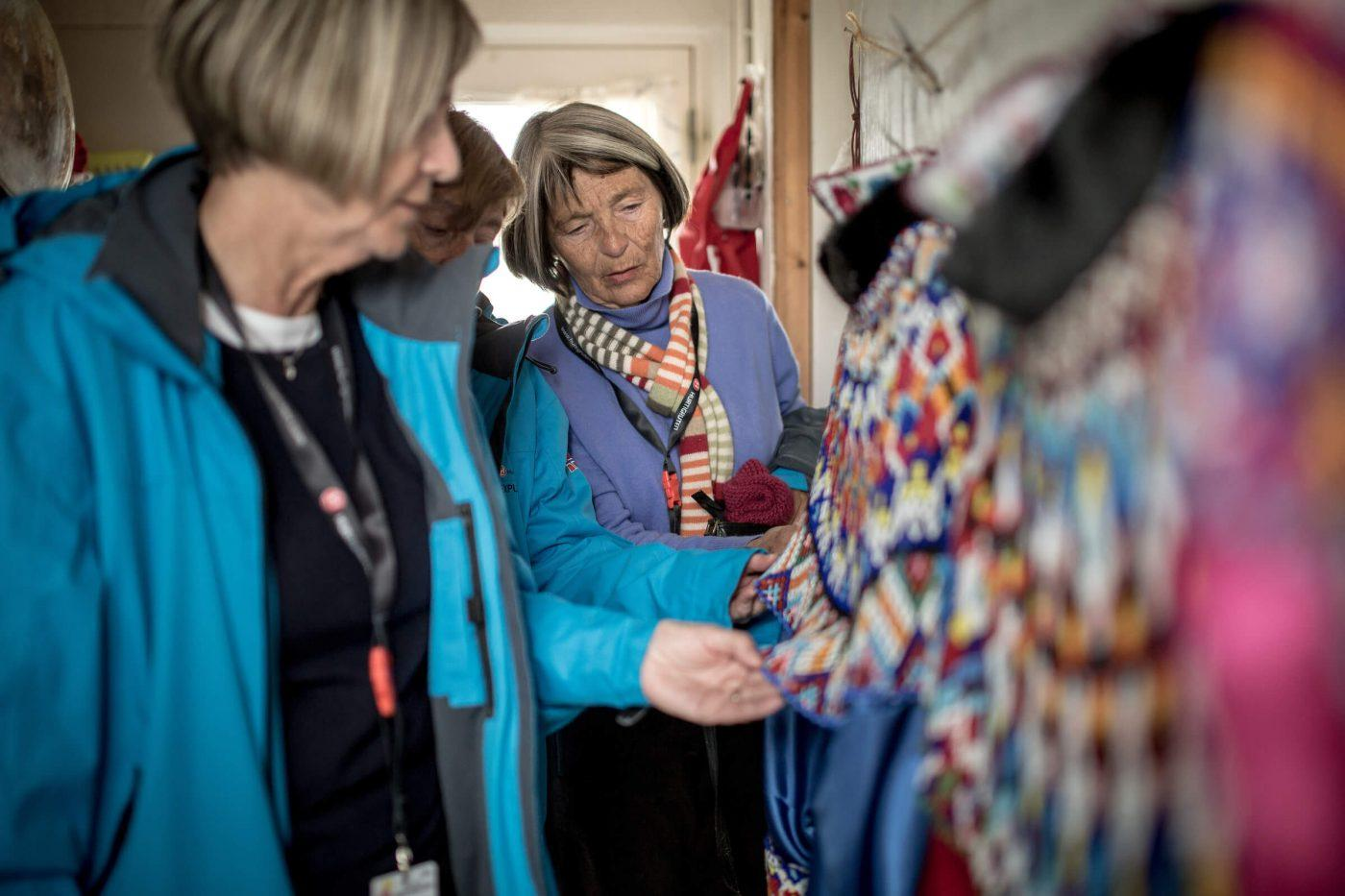 MS Fram cruise guests looking at national costumes in Itilleq in Greenland. Photo by Mads Pihl