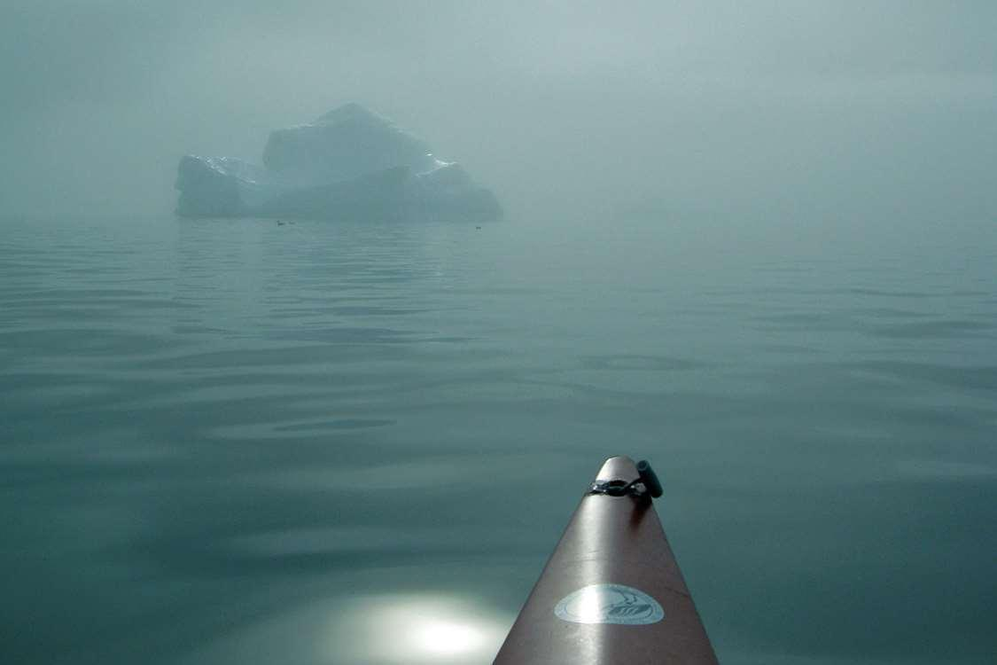 Gloomy day on sea in South Greenland with an iceberg in the background and the tip of a kayak in the foreground. Photo by Nanortalik Tourism Service