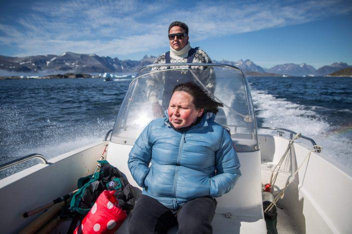 Man sailing a dinghy while a woman sits in front of him in South Greenland. Photo by Nanortalik Tourism Service