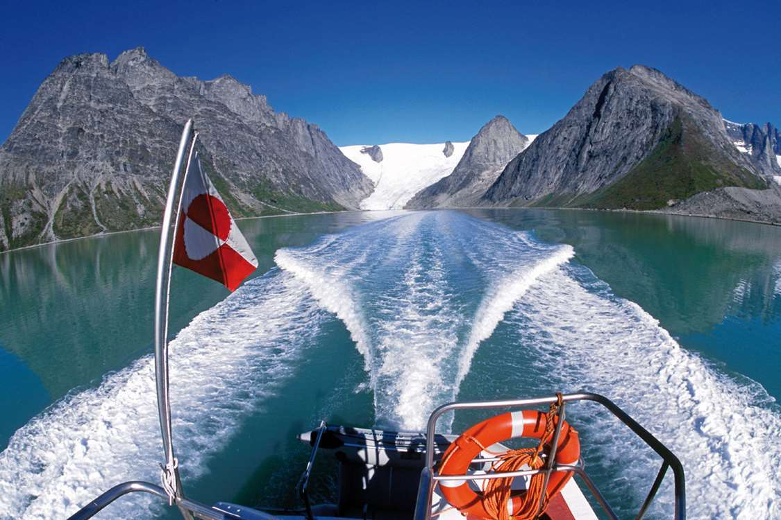 Glacier view from boat with a Greenlandic flag in foreground in Summer. Photo by Nanortalik Tourism Service