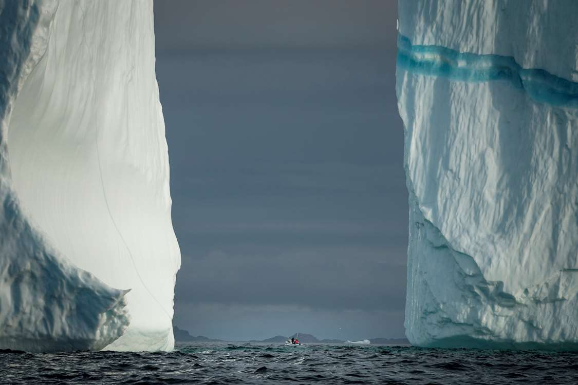 Two iceberg walls and a tiny boat near Kulusuk in East Greenland. Photo by Mads Pihl - Visit Greenland