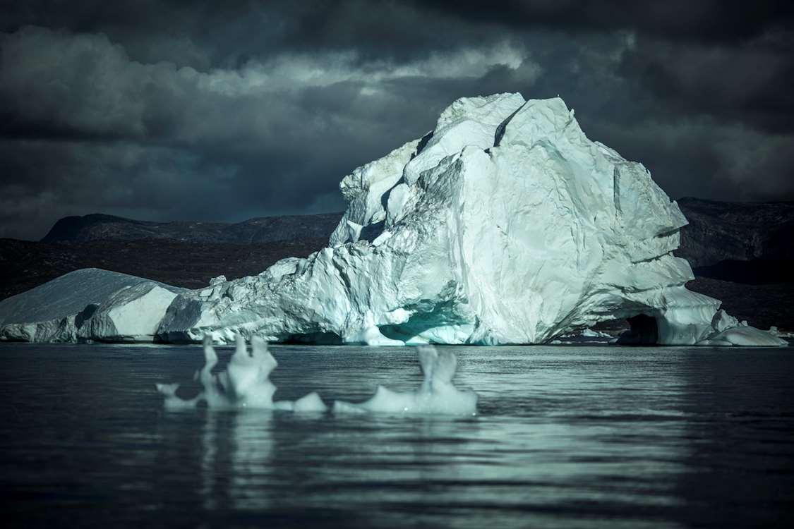 An iceberg under dark clouds in the Disko Bay in Greenland. Photo by Mads Pihl - Visit Greenland