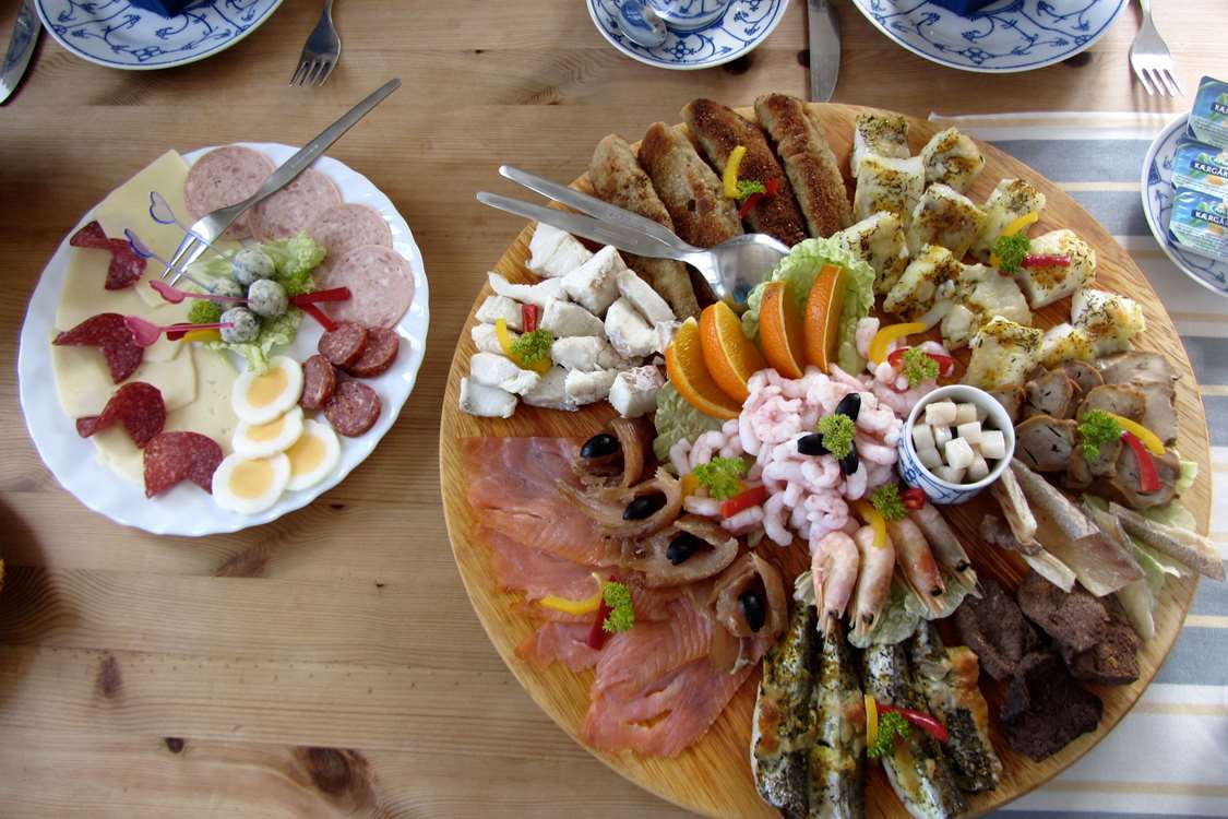 Two plates with food - a mix of local Greenlandic delicatessens and imported fruit and meat. Photo by North Greenland Adventure
