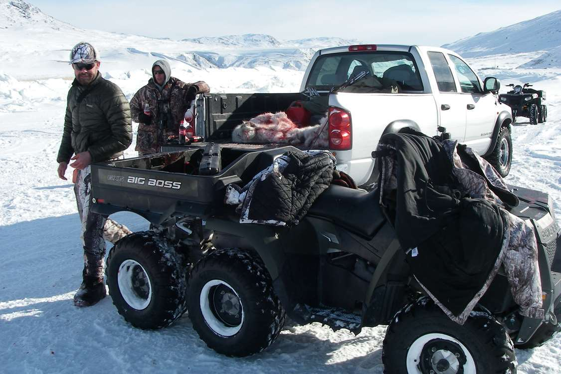 Hunters standing beside ATV and truck with reindeer fur in trunk. Photo by North Safari Outfitters