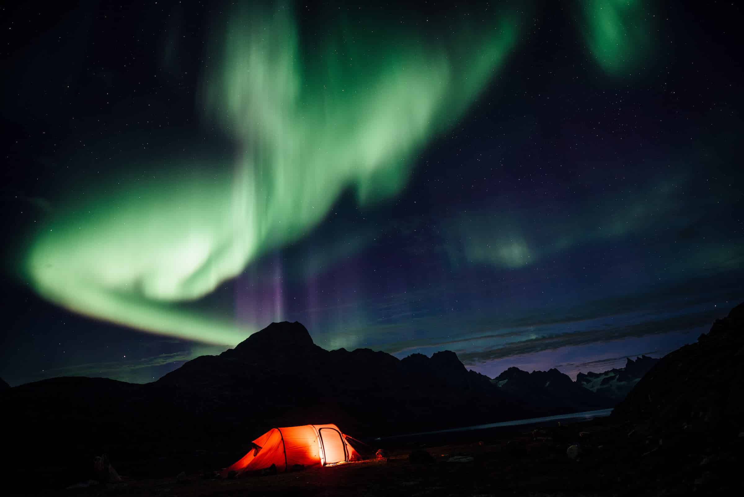 Northern lights over a lit tent, Camp In Tasiilaq Fjord. By Chris Brinlee Jr