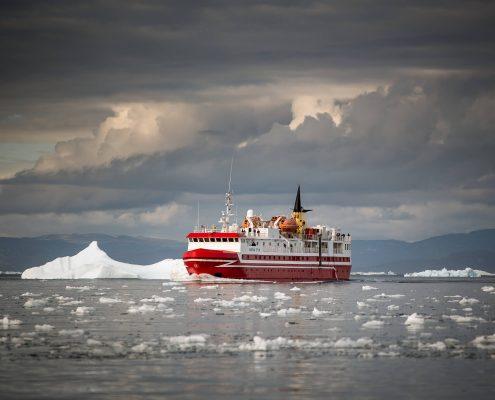 Passenger ferry Sarfaq Ittuk in the Disko Bay under dramatic clouds in Greenland. By Mads Pihl