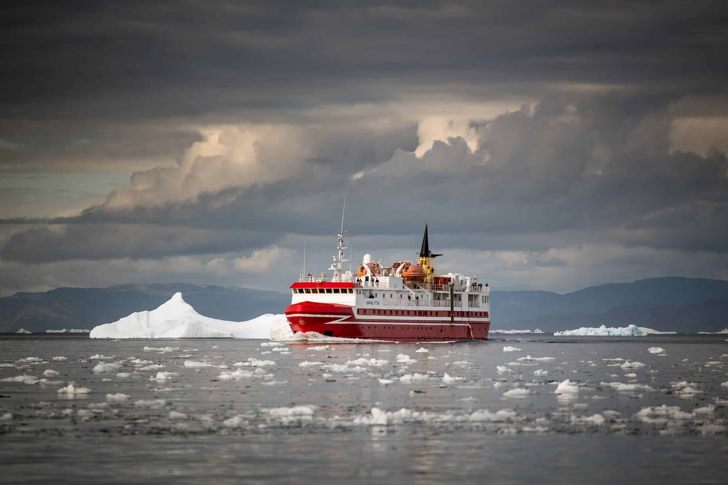 Passenger ferry Sarfaq Ittuk in the Disko Bay under dramatic clouds in Greenland. By Mads Pihl