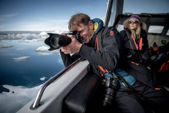 A photographer shooting icebergs and ice near Tiniteqilaaq in East Greenland. By Mads Pihl