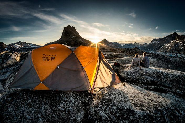 Sunset over two hikers near a tent camp at Qernertivartivit in East Greenland. By Mads Pihl