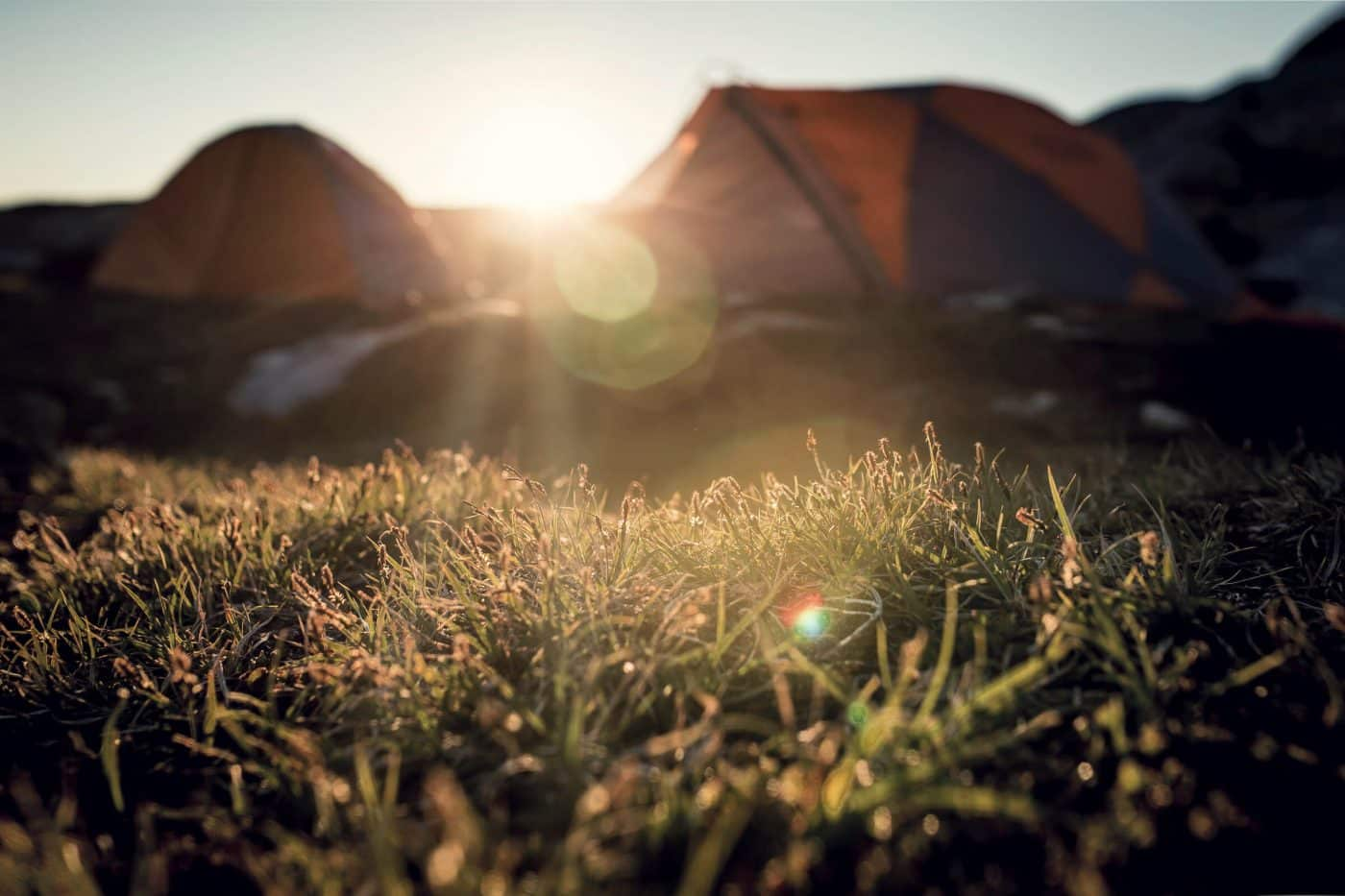 The midnight sun behind two tents in East Greenland. By Mads Pihl