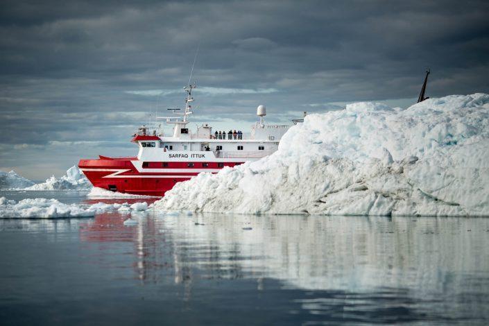 The passenger ferry Sarfaq Ittuk passing behind an iceberg near Ilulissat in Greenland