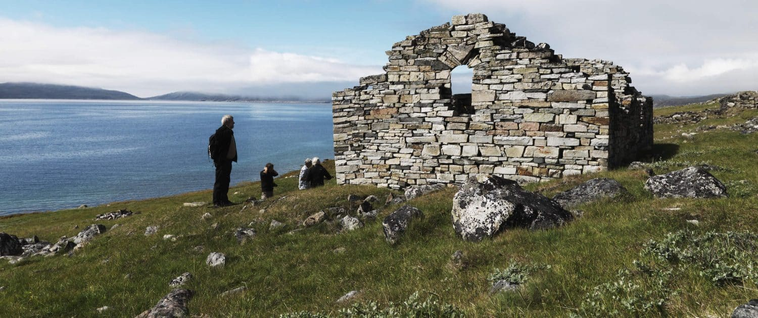 Travelers studying the 1000 year old Hvalsey church ruin in south Greenland not far from Qaqortoq. By David Trood