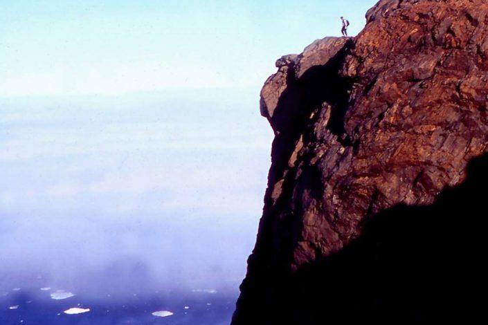 A hiker on a cliff looking across the water. Photo by Arctic Dream, Visit GreenlandArctic Dream Travellodge Greenland 10